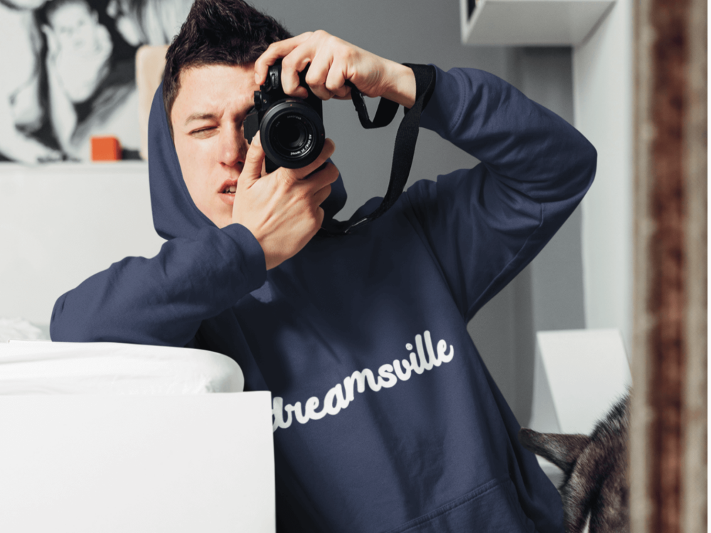 Man holding camera and wearing Dreamsville blue hoodie