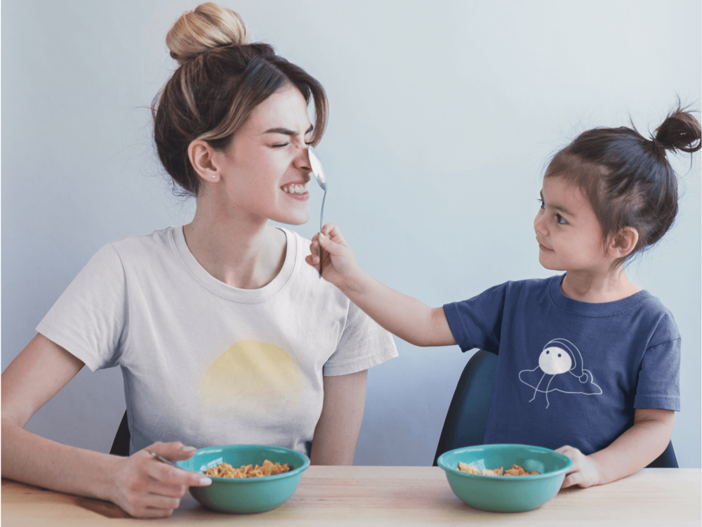 Kid eating breakfast with mom wearing the Dreamsville organic cotton t-shirt